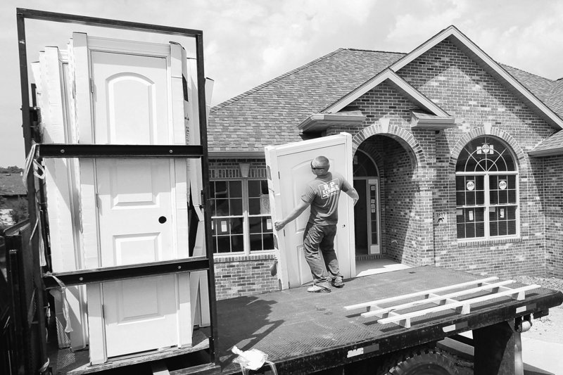 Construction worker Brian Stocks unloads doors at a home being built in Springfield, Ill.