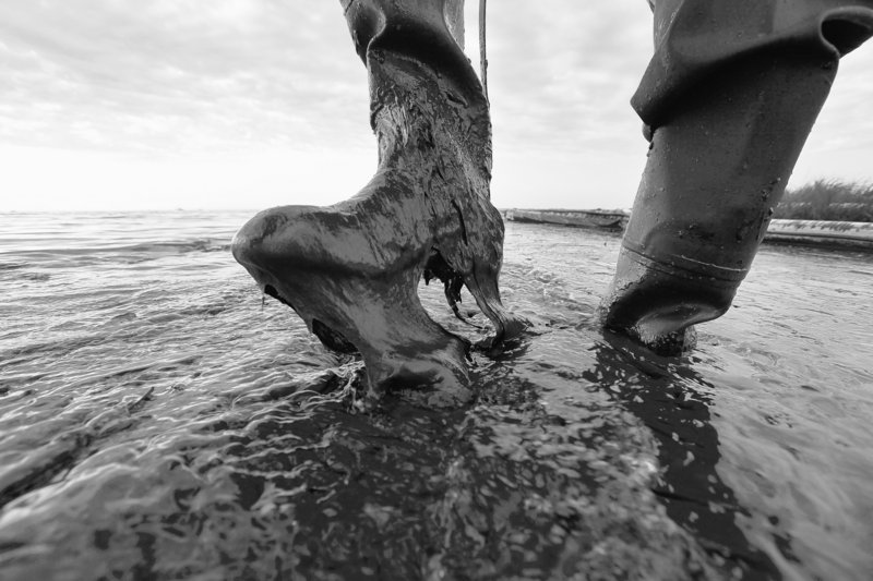 Boots not made for walking in thick beached oil are worn by Plaquemines Parish, La., coastal zone director P.J. Hahn at Queen Bess Island in Barataria Bay. After three long months, the bleeding from the bottom of the Gulf of Mexico has finally been stanched. But in many ways, the prognosis remains uncertain.
