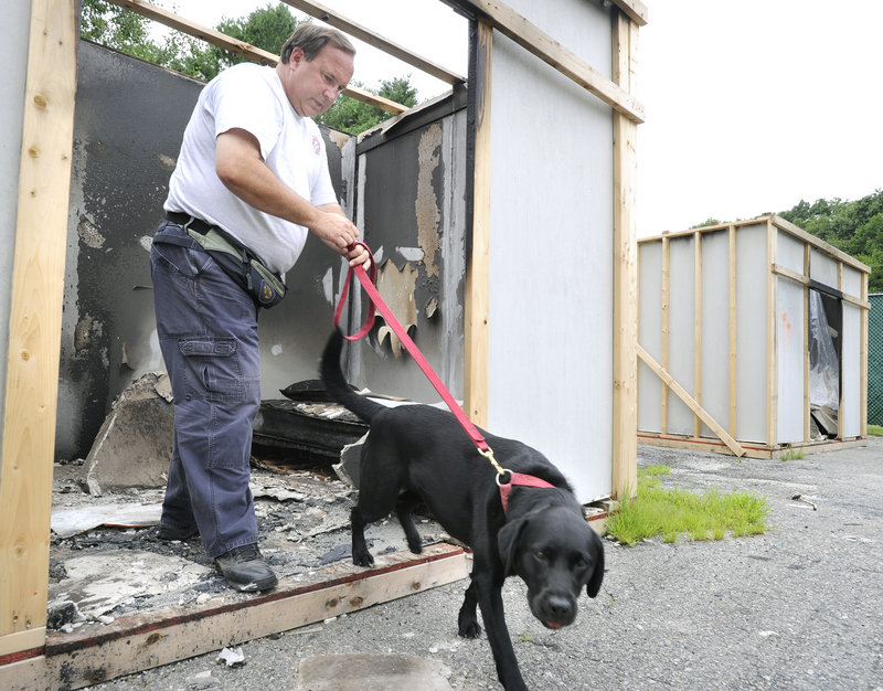 Investigator Rick Shepard of the state Fire Marshal's Office and his dog Shasta work a staged fire scene Tuesday as they and other arson teams train at a facility in Yarmouth.