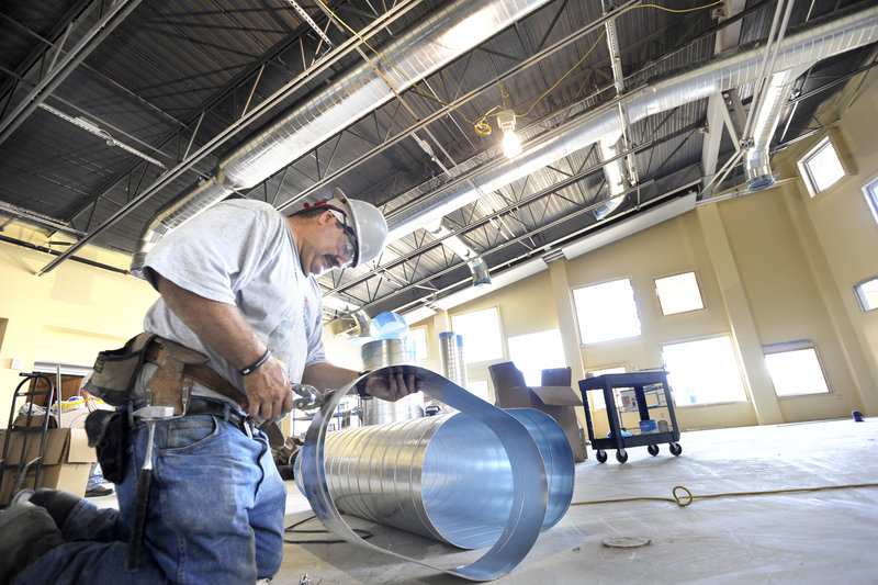 Raymond Roy cuts ductwork for the cafeteria of the school, which is expected to be completed by Thanksgiving.