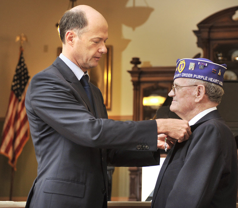 "Elvert Pooler receives the Legion of Honor medal Wednesday from Christophe Guilhou, consul general of France in Boston, at the Sanford Springvale Historical Museum. ""Pooler was ready to sacrifice himself for France,"" Guilhou said."