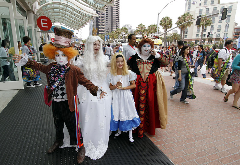 """A family dressed as characters from """"Alice in Wonderland"""" pose for a photo outside of the Comic-Con International Thursday in San Diego."""
