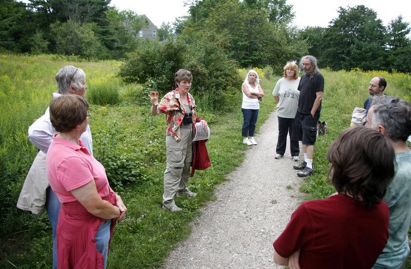 Portland Trails advisory board member Lois Winter leads a tour of Portland's Capisic Park on Friday, explaining a plan to rip up the trail as part of a sewer line upgrade. City workers are preparing to replace and separate sewers that send untreated sewage into Casco Bay during heavy rains.