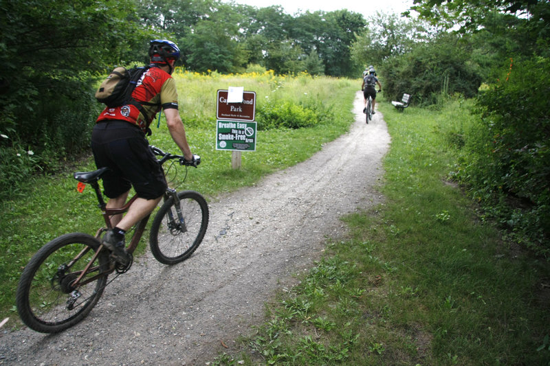 Mountain bikers enter Capisic Park near Macy Street on Friday. After a sewer project, which starts next month, is carried out, 600 new trees and shrubs will be planted in the park.