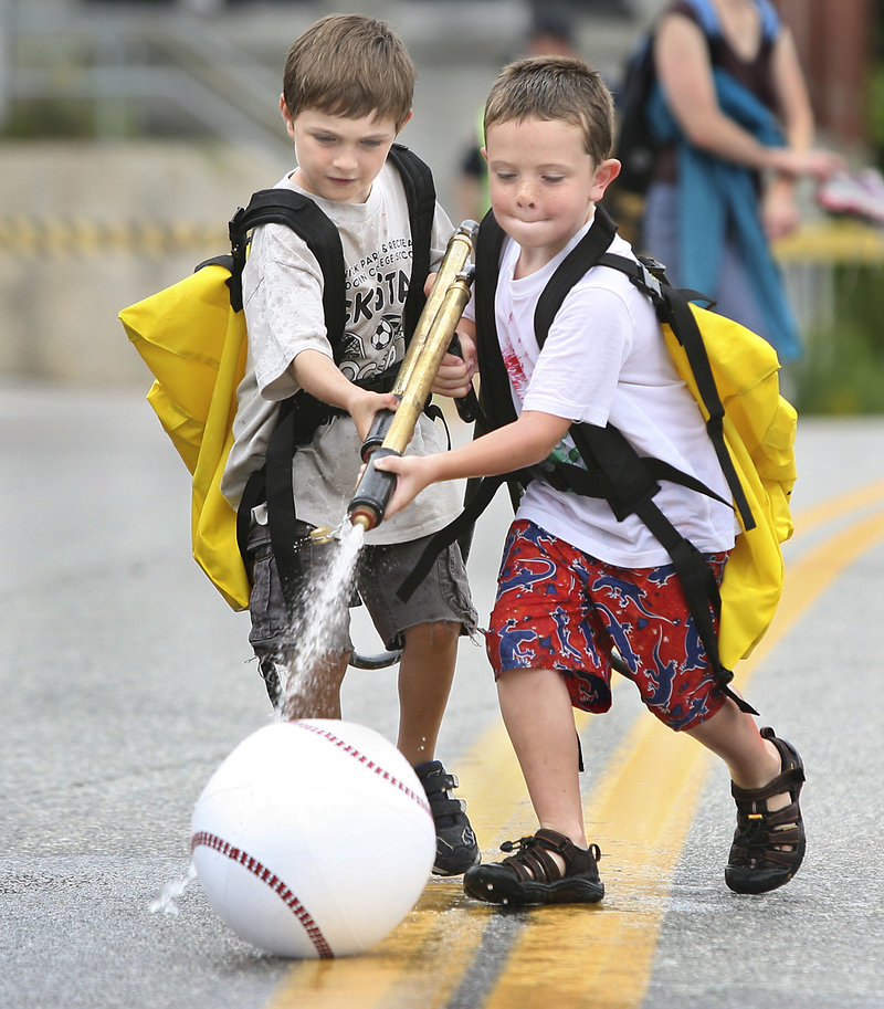 Caden Slater, 5, of Brunswick, left, and Cole Alexander, 6, of Richmond use water backpacks to spray an inflatable ball down the street. The game was sponsored by the Richmond Fire Department.