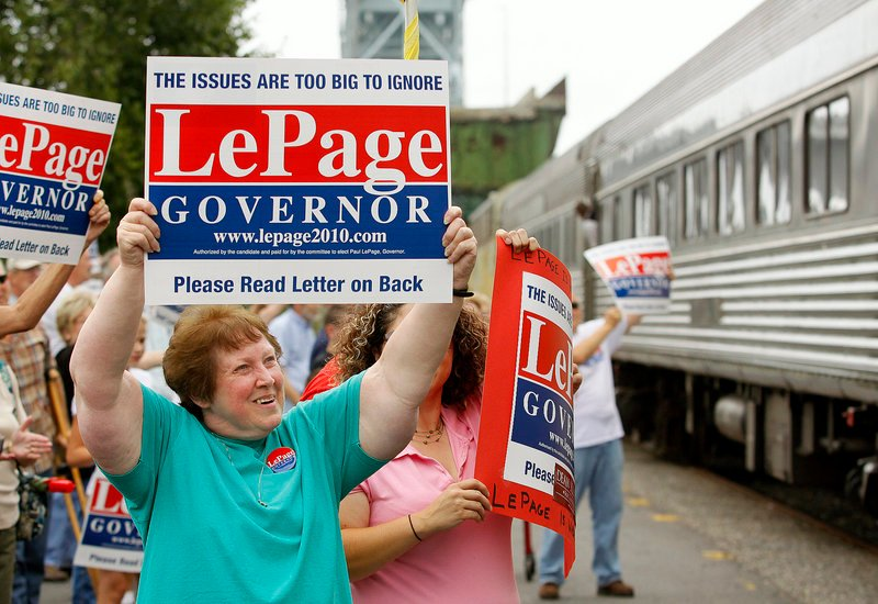 Ruthe Pagurko of Bath holds up a sign as candidate for governor Paul LePage stops in Bath on a train tour.
