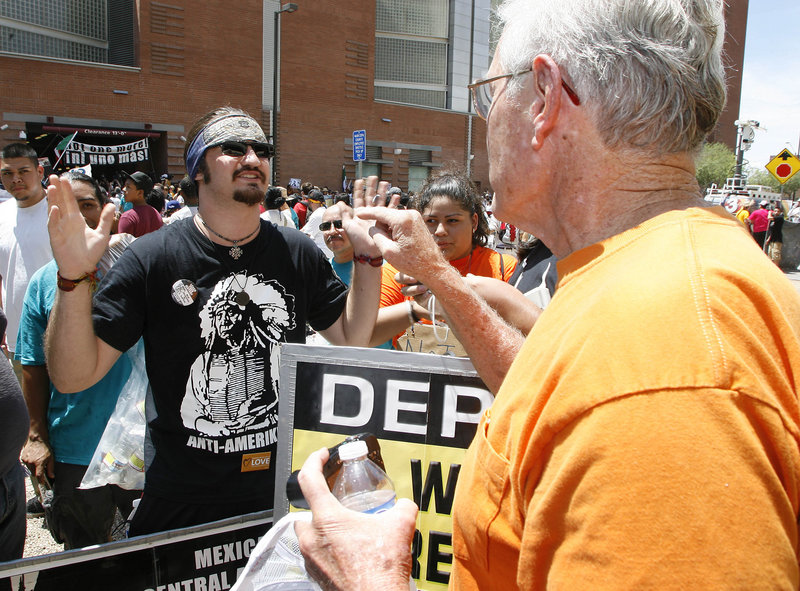 A supporter of Arizona's immigration law, left, engages in an impromptu debate with an opponent Thursday in Phoenix, Ariz.