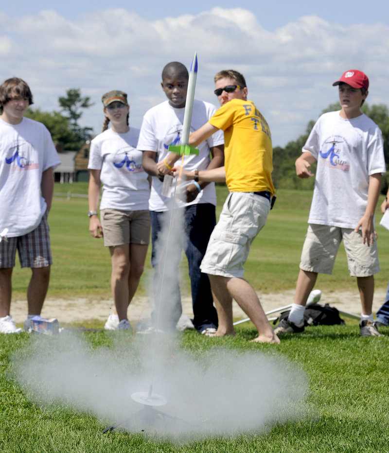 Damien Kayamba, 14, of Portland and instructor Ben Ingraham in yellow, both center, launch a rocket at Twin Brook Recreational Area in Cumberland on Friday. Ten students, ages 10 to 14, attended the city-run Aviation Career Exploration Academy.