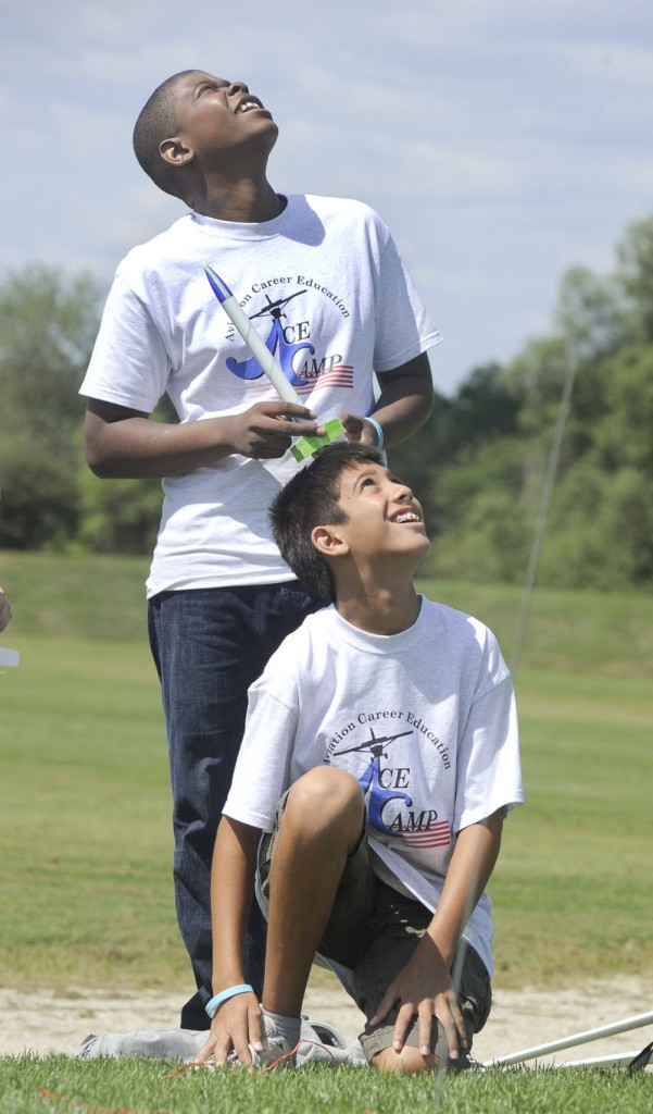 Trystan Bates, 12, of Gorham, kneeling, watches his rocket soar as Damien Kayamba waits his turn. The ACE Academy program was established by the FAA to generate interest in aviation.