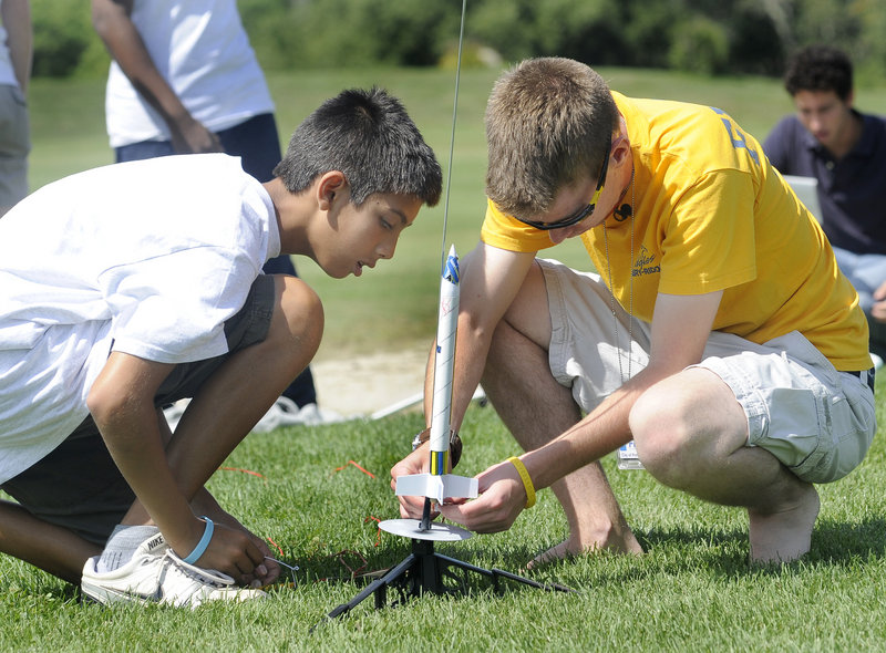 """Trystan Bates, 12, of Gorham, left, watches as instructor Ben Ingraham prepares to launch a rocket at Twin Brook Recreation Area in Cumberland on Friday. """"This camp is like one big field trip,"""" said Adam Godfrey, 11, of Yarmouth."""