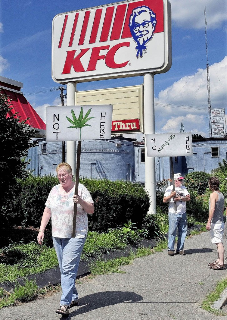 Beverly and Andrew Busque picket outside the former KFC restaurant in Waterville on Thursday. The site is where a proposed medical marijuana dispensary may be located. Beverly Busque said she approves of medical marijuana but is not in favor of the site, adjacent to her property.