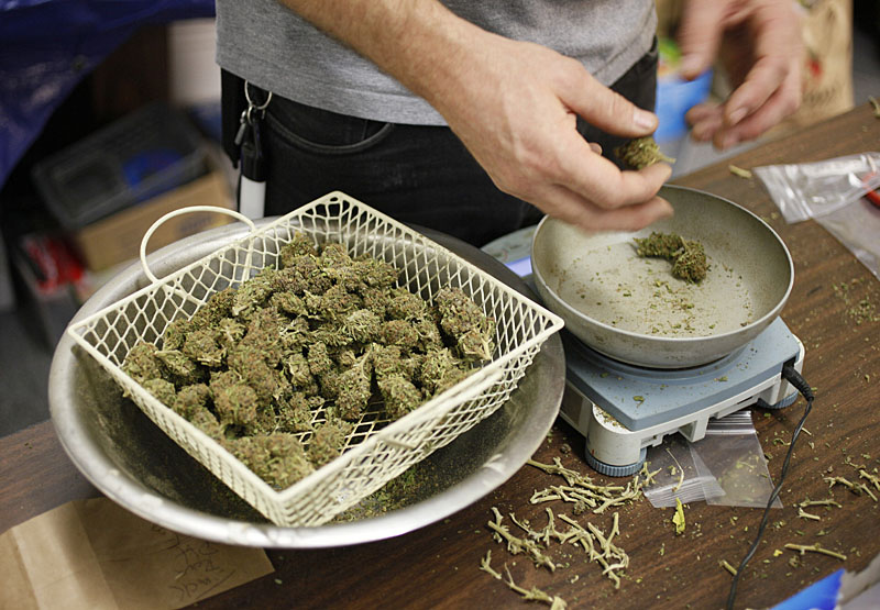 In Maine, dispensaries are planning to price their pot at $300 to $400 an ounce, which is reportedly what the drug costs on the street. In this photo, a worker at a San Francisco marijuana clinic prepares packets of marijuana buds for sale.