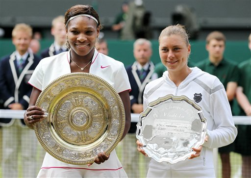 Serena Williams, left, of the United States holds her winners trophy as she stands next to runnerup Russia's Vera Zvonareva after their women's singles final at the All England Lawn Tennis Championships at Wimbledon, Saturday, July 3, 2010. (AP Photo/Alastair Grant)