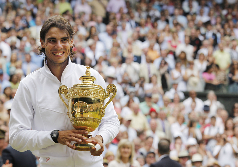 Rafael Nadal smiles as he holds his trophy after defeating Tomas Berdych of the Czech Republic in the men's singles final at the All England Lawn Tennis Championships at Wimbledon today.