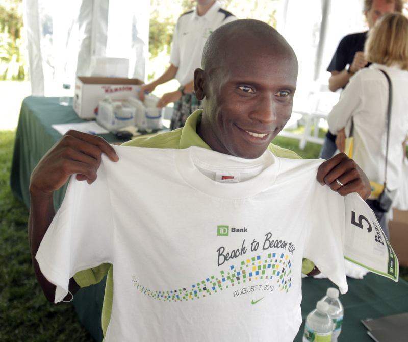 Boaz Cheboiywo holds up his Beach to Beacon shirt to see if it's the right size after the news conference for the TD Bank Beach to Beacon 10K road race in Cape Elizabeth on Friday.