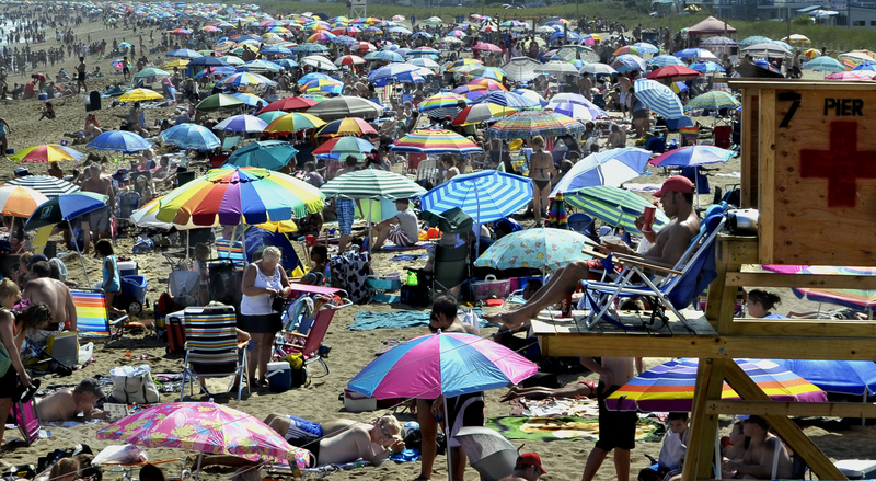 Perched above a sea of people and parasols, lifeguard Lance Timberlake monitors the scene at Old Orchard Beach on Tuesday. During the school year, Timberlake teaches American history and psychology at Sanford High School.