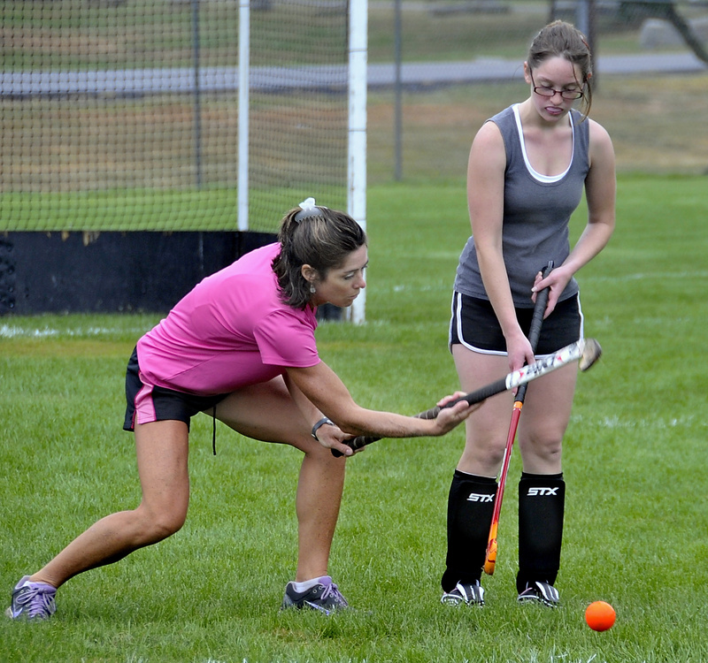 Leslie Mourmouras, Biddeford's new field hockey coach, gives instructions to Josie Rhoy.