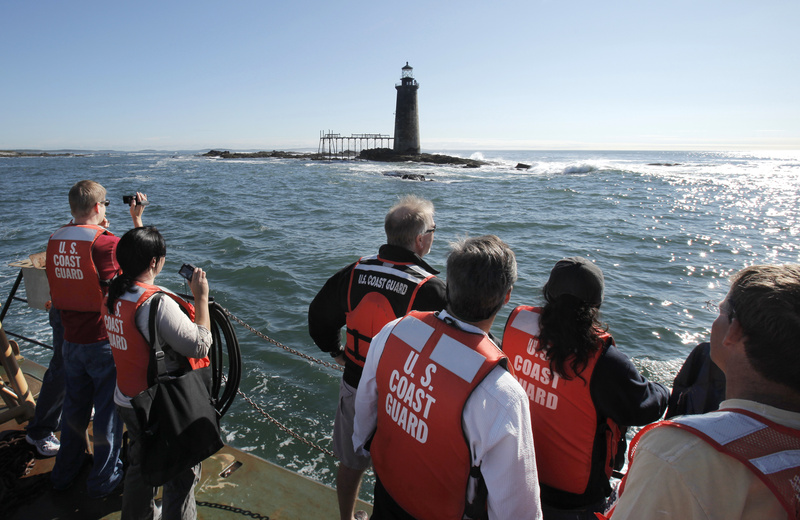 Bidders and their companions check out Ram Island Ledge Light on Thursday from a vessel provided by the Coast Guard. The seas were too rough for the boat to land on the rocky ledge and let bidders disembark to tour the interior, so they had to settle for viewing from a distance.