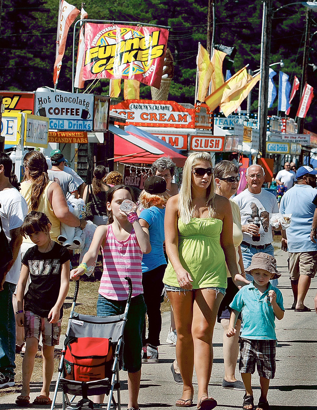 A crowd of all ages navigates the midway at the fair Saturday, partaking of food and beverages that appealed to a crowd of, well, all ages.