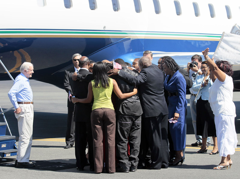 Aijalon Gomes' family huddles around him after his arrival with former President Jimmy Carter, left, at Logan International Airport.