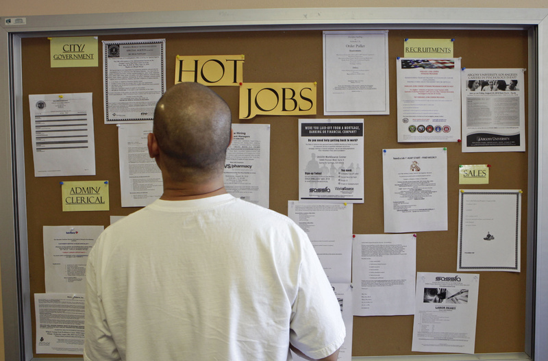A job seeker checks for new jobs postings at the Glendale Workforce Services Center this month in Glendale, Calif. The nation's large-scale stimulus measure has created or saved as many as 3.3 million jobs and continues to boost economic growth in the second half of 2010, the Congressional Budget Office says, but it comes with a high pricetag.
