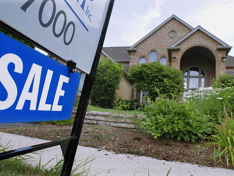 "A ""For Sale"" sign is displayed outside a home in Springfield, Ill. Despite the lowest mortgage rates in decades, homes are quickly returning to their prewar status as places to live rather than sources of wealth."