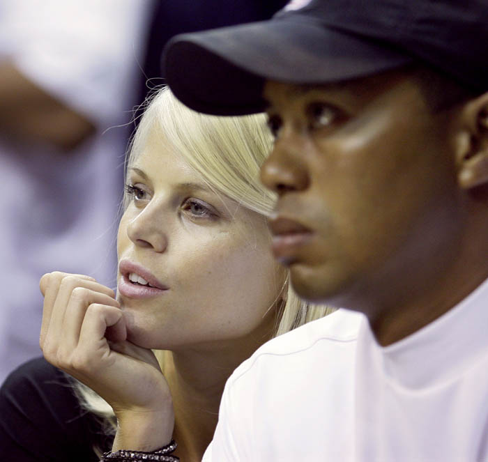 In this June 2009 photo, Elin Nordegren talks to her then-husband, golfer Tiger Woods during an NBA basketball game in Orlando, Fla.