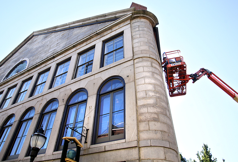 Mark Dussault and Michael Gombos of D & G Restoration repair a window Monday in the Mariner's Church on Fore Street in Portland. The company is repairing water-damaged windows and restoring the exterior of the building, which was built in 1829.
