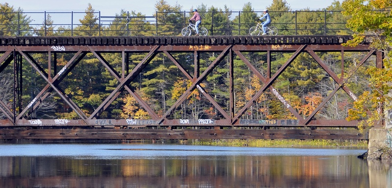 Bicyclists cross a railroad bridge over the Presumpscot River. When converting a rail line to a bike or walking path, it's important not to preclude its return to rail use.