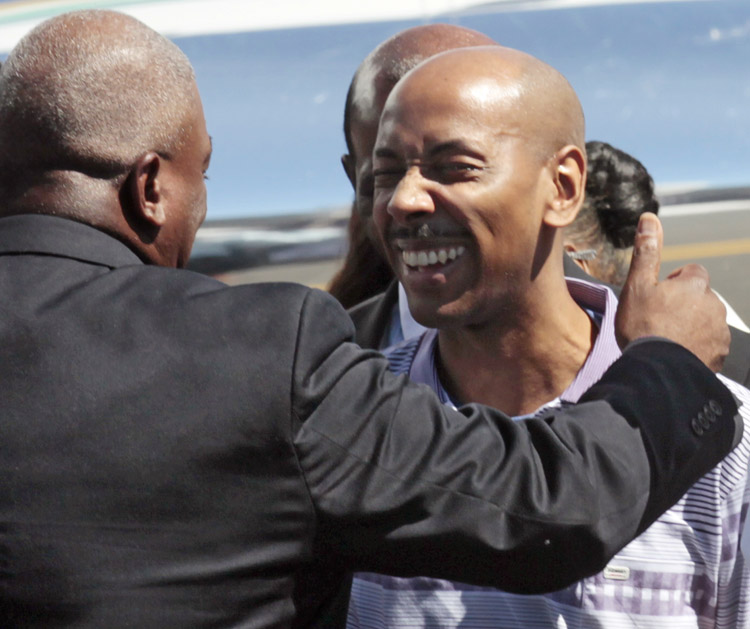 Aijalon Gomes is greeted by family members after arriving with former President Jimmy Carter at Logan International Airport in Boston today.