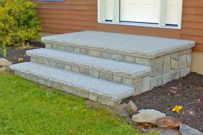 Composite materials that look like wood make durable steps too, but can be pricey. Concrete steps are usually less expensive than cut stone steps, such as those made of granite.