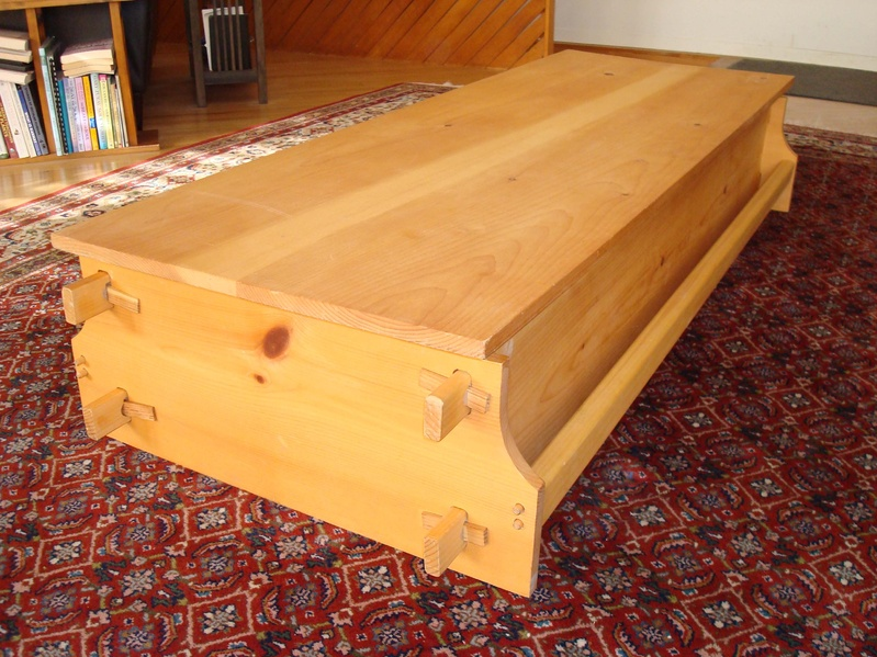 The wedged coffin, made by Chuck Lakin of Waterville, can be stood on end and used as a bookcase, display shelf or a wine rack, or on its back and used as a storage chest and/or coffee table like here.