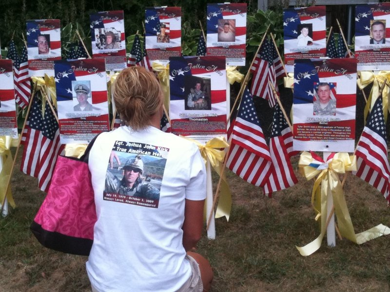 Elizabeth Fulton, whose brother died in Afghanistan, kneels before markers at Veterans' Park in Ogunquit today before the Run for the Fallen, a noncompetitive run from Ogunquit to Portland to commemorate soldiers who have died since the Sept. 11, 2001 terrorist attacks.