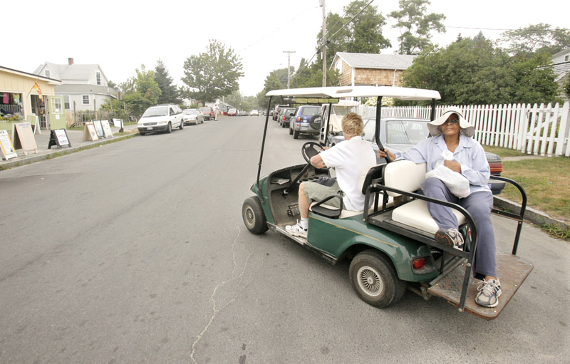 Matt Rand gives a ride to Meikie Jenness on Peaks Island on Aug. 5. Rand said his golf cart is inspected and insured, as required for all golf carts that travel on city roads. But he doesn't have liability insurance for his passengers.