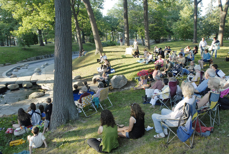 "Audience members for ""Twelfth Night"" sit on their own chairs and blankets under the trees of Deering Oaks. It's a casual atmosphere for a high-quality performance."
