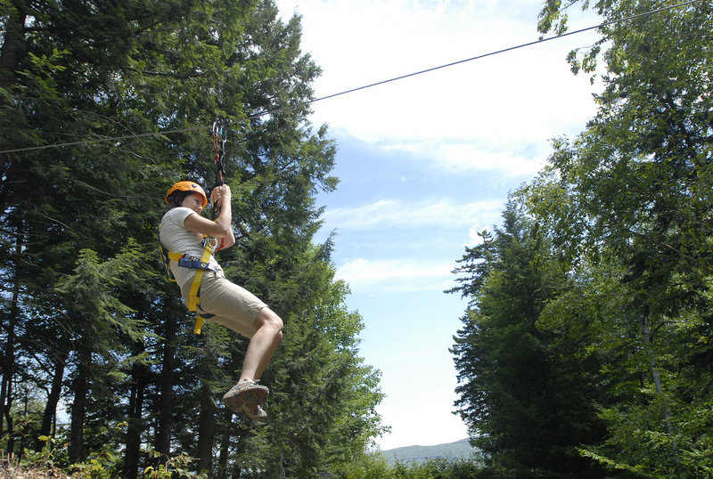 Sunday River's director of communications, Darcy Liberty, glides down a zip line.
