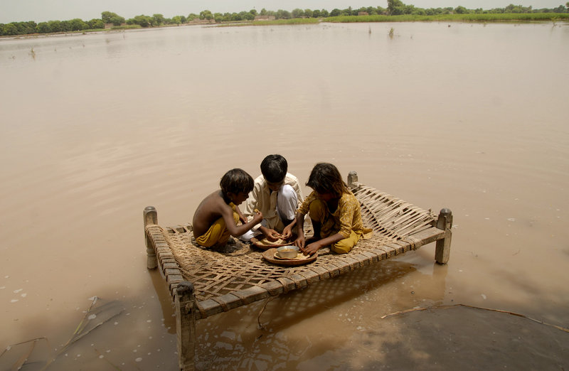 Pakistani children sit on a bed to eat in the flood-hit area of Qasim Bella on Saturday.