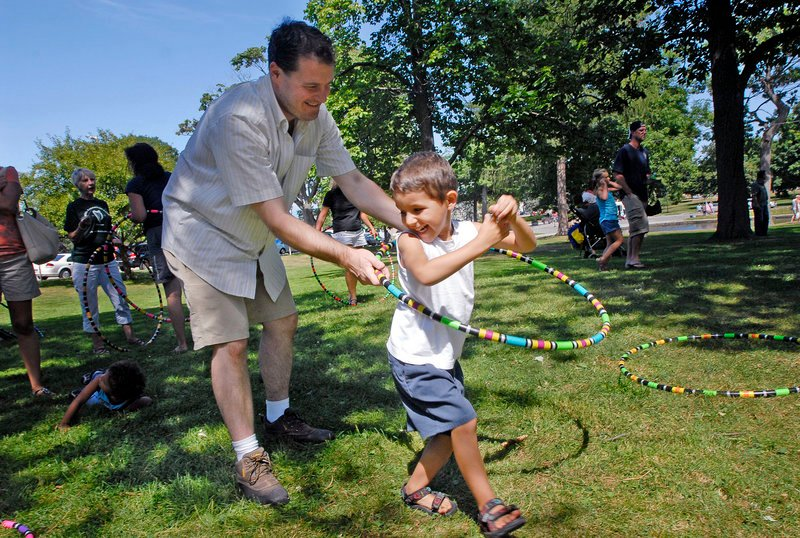 Benicio Collings, 4, of Portland gets some help with a hula hoop from his father, Ben Collings, during the Festival of Nations in Deering Oaks in Portland on Saturday. Tracy Tingley of Hardcore Hoops in Portland provided the hoops for the event.