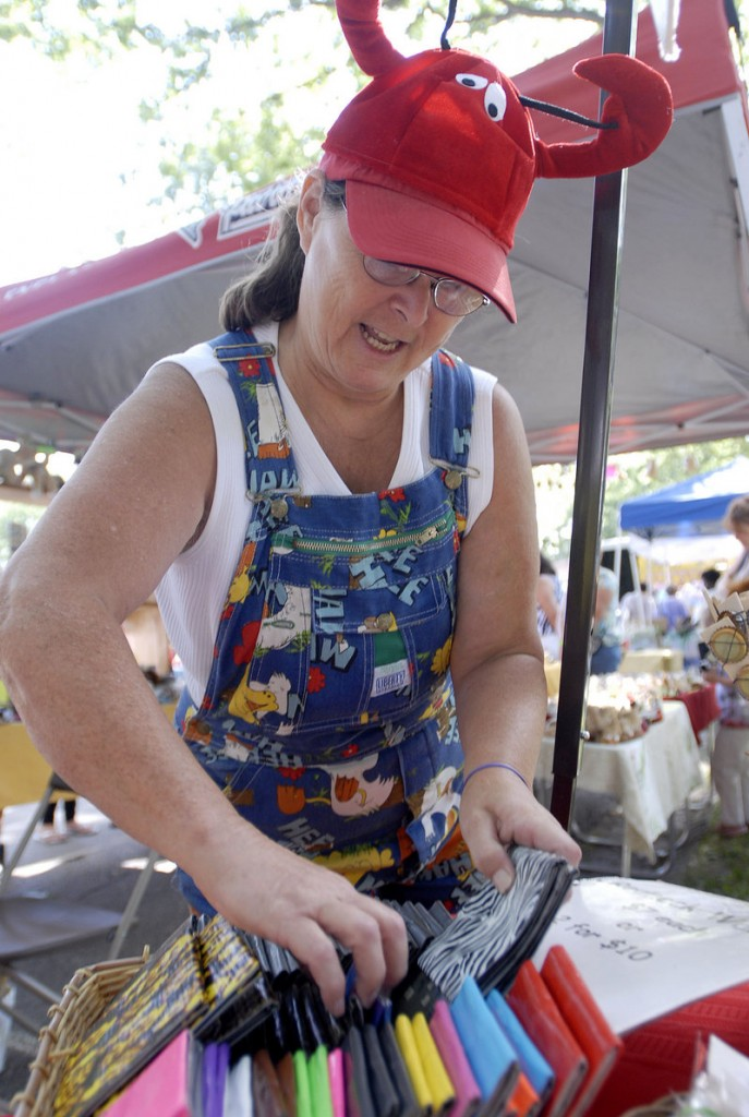 """Linda Austin of Lisbon Falls arranges her """"redneck wallets"""" – made of duct tape – at her booth at the eighth annual Festival of Nations in Deering Oaks on Saturday."""