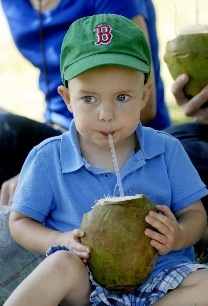 Noah Timmins, 2, of Portland enjoys coconut juice fresh from the fruit at the Festival of Nations. Saturday's event included vendors of ethnic food and crafts as well as dance and music performances.