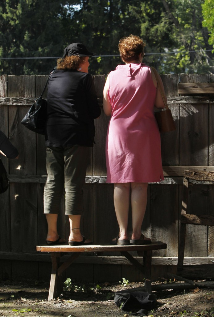 Two women stand on a bench to get a view of guests leaving the Delamater Inn on their way to Chelsea Clinton and Marc Mezvinsky's wedding on Saturday.