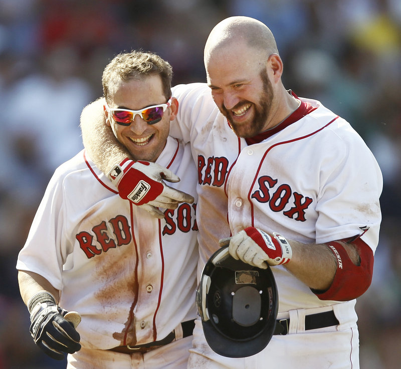 Marco Scutaro, left, gets a hug from Kevin Youkilis after Scutaro's bunt single in the bottom of the ninth scored Darnell McDonald and sent the Red Sox past the Tigers, 4-3.