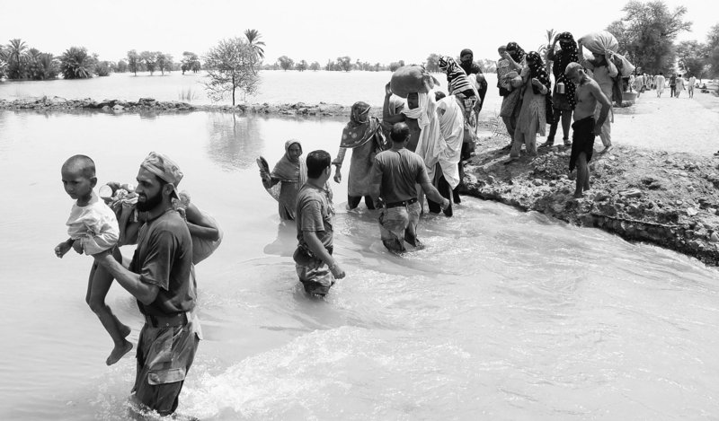 Pakistani soldiers help people to ford water as they flee their village flooded by heavy monsoon rains near Multan, Pakistan, on Sunday. More than 27,000 people remained trapped in one province, and 43 military helicopters and 100 boats were deployed to save them.