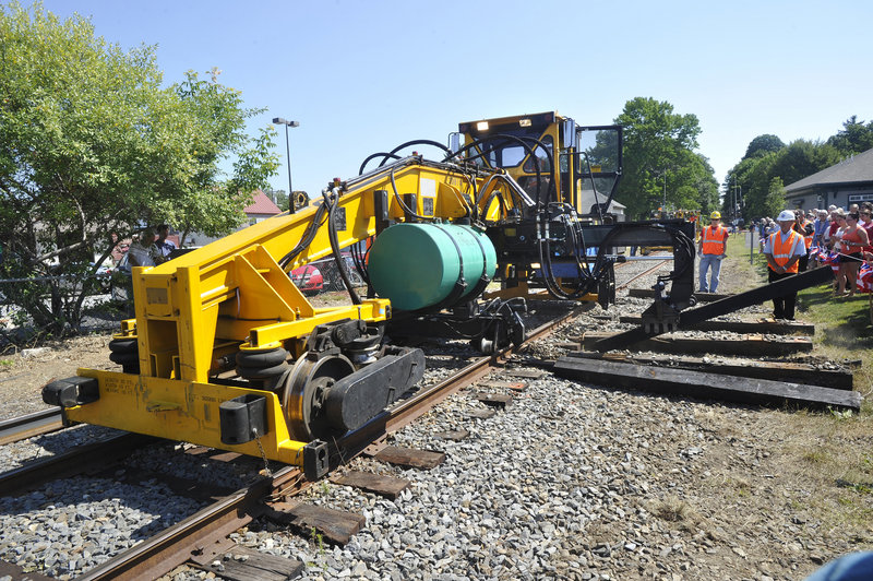 Railroad construction crews demonstrate how old rail ties are removed and replaced with new ones Monday, when work began on tracks to extend the Downeaster train service from Portland to Brunswick. The expanded service is scheduled to begin in the fall of 2012.