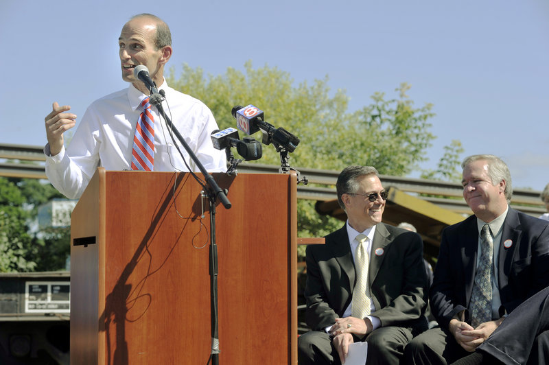 Gov. John Baldacci addresses several hundred people on hand to mark the beginning of the expansion of the Downeaster train service. Seated, from left, are Joseph Szabo, head of the Federal Railroad Administration, and state Transportation Commissioner David Cole.