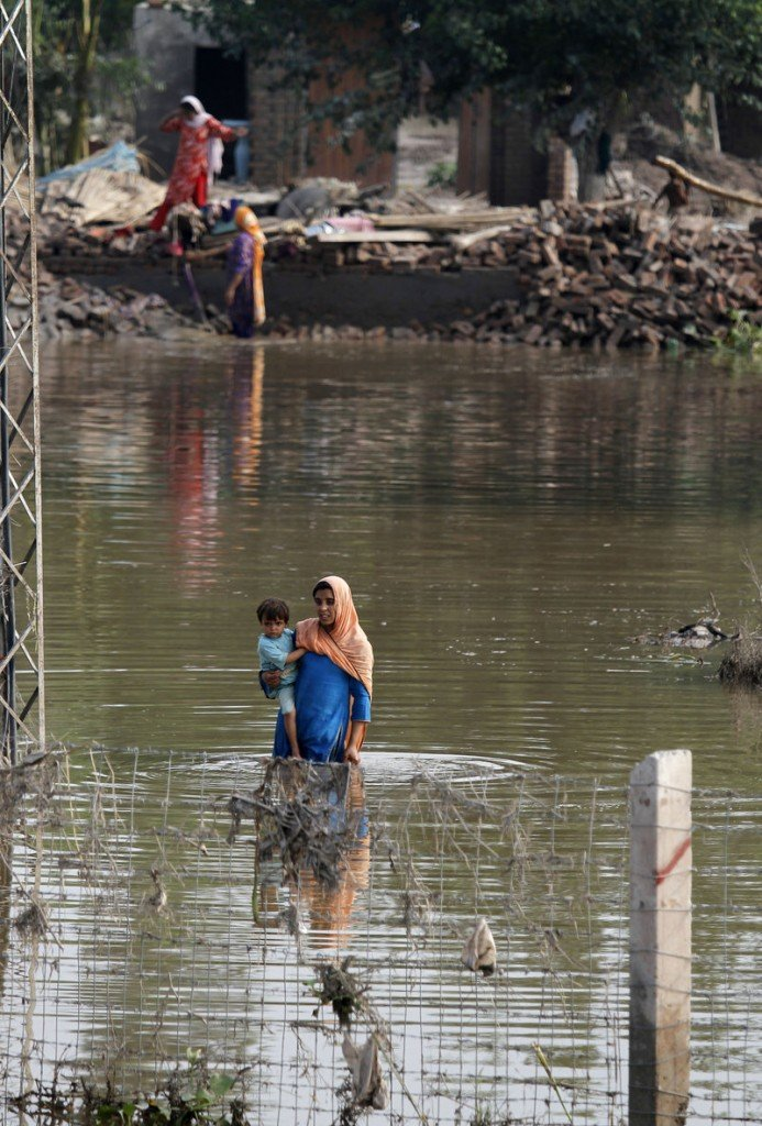 A woman carries her child as she wades through floodwater next to her collapsed house in Kamp Karoona village, Pakistan, on Monday.
