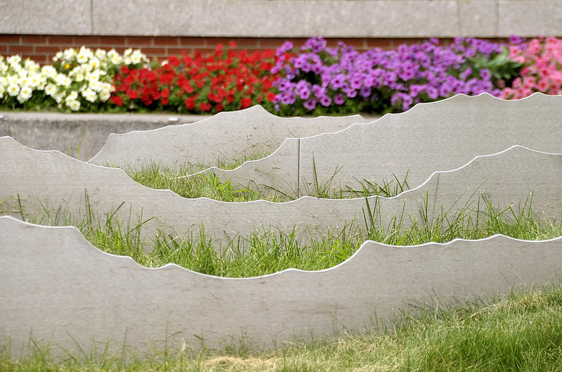 """""""Tracing the Fore,"""" installed in 2007, consists of stainless steel waves emerging from a bed of sculpted fescue grass, which is supposed to grow tall and rustle in the wind to resemble the river's waves. The problem is, the grass has never taken."""