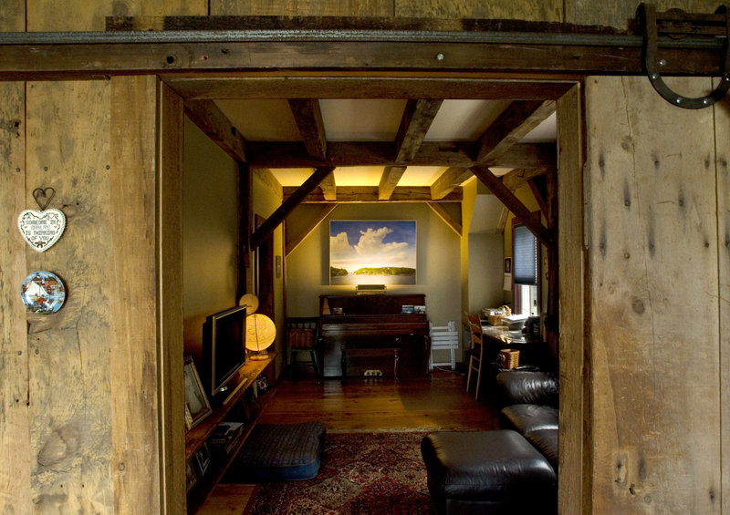 An old barn door rolls open to reveal a home office.