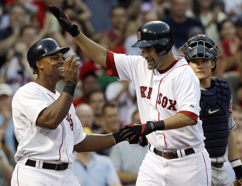 Mike Lowell, right, is welcomed by Adrian Beltre of the Boston Red Sox after returning from the disabled list with a two-run homer in the second inning of a 3-1 victory.