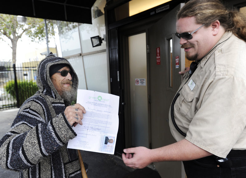 Richard Lahrson of Berkeley, Calif., shows his doctor's recomendation and an identification card to Paul J. White before entering the Berkeley Patients Group clinic in Berkeley.